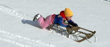 Winterurlaub und Schlittenfahren im Schnee